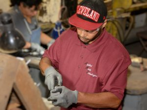 An employee grinding castings to meet final finishing requirements