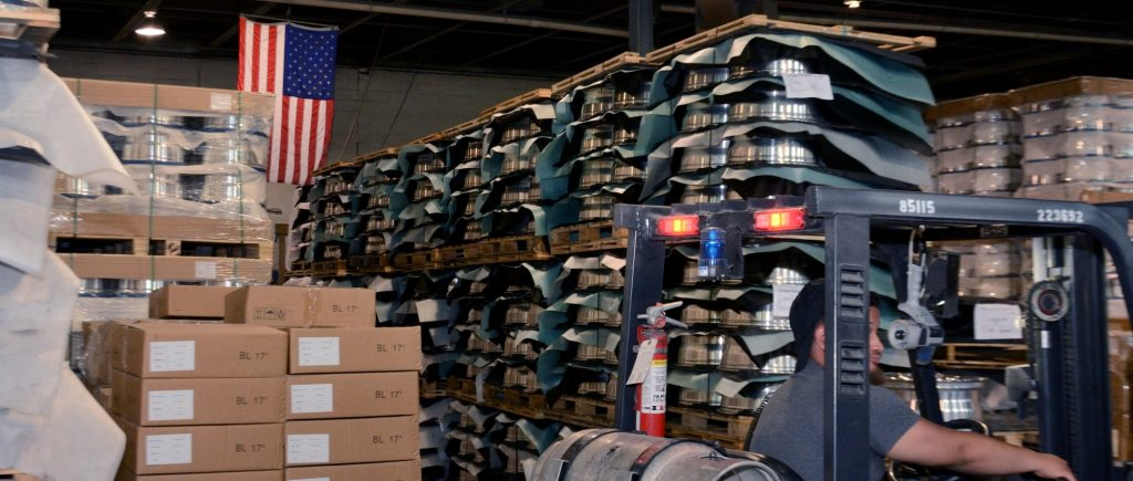 AMT warehouse with US flag, pallets of wheels, and forklift