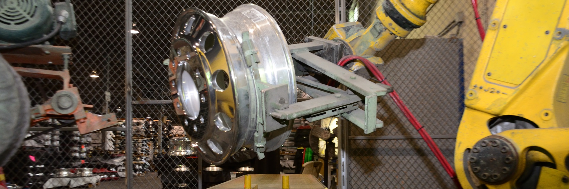 Robotic arm carrying heavy truck wheel to buffer