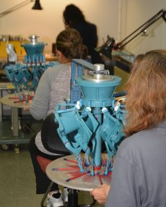 Employees assembling wax patterns onto an investment casting tree